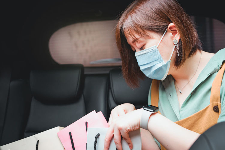 Close-up of woman wearing mask sitting with shopping bags in car