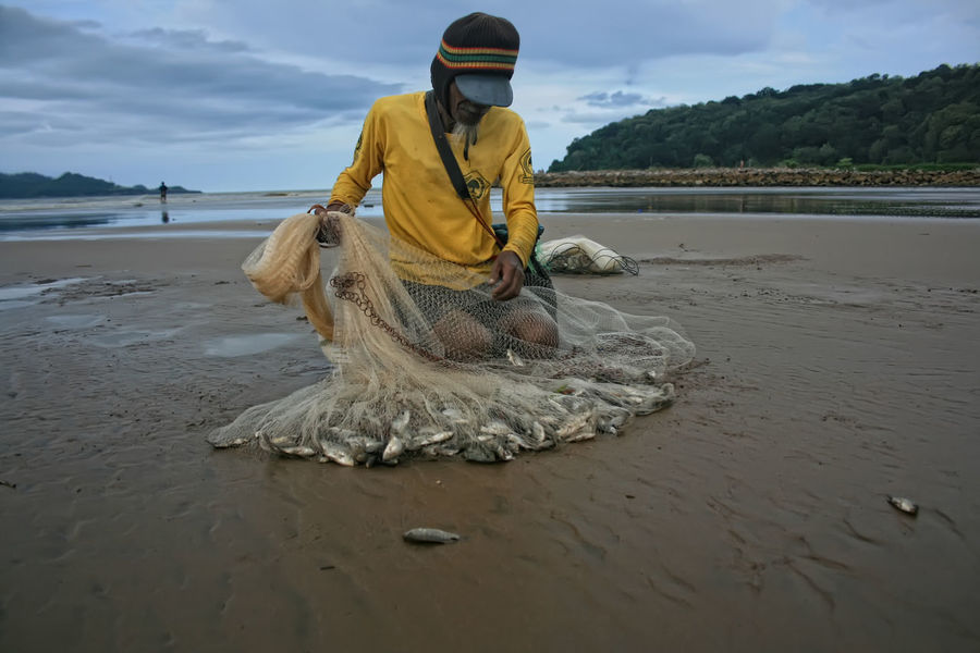 traditional fisherman in pacitan eastjava Indonesia Beach Beauty In Nature Day Fish Fisherman Nature Nautical Vessel One Person Outdoors Real People Sand Scenics Sea Shore Sky Water Investing In Quality Of Life
