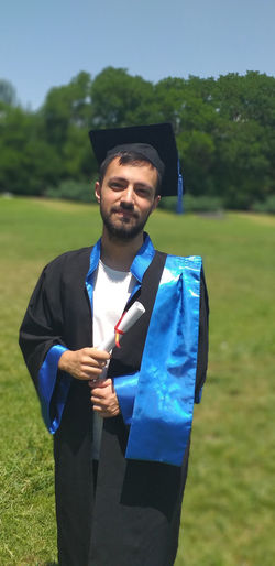 Portrait of young man wearing graduation gown while standing on land