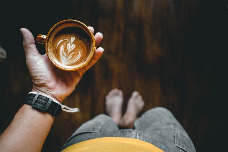 Low section of man having coffee while standing on hardwood floor
