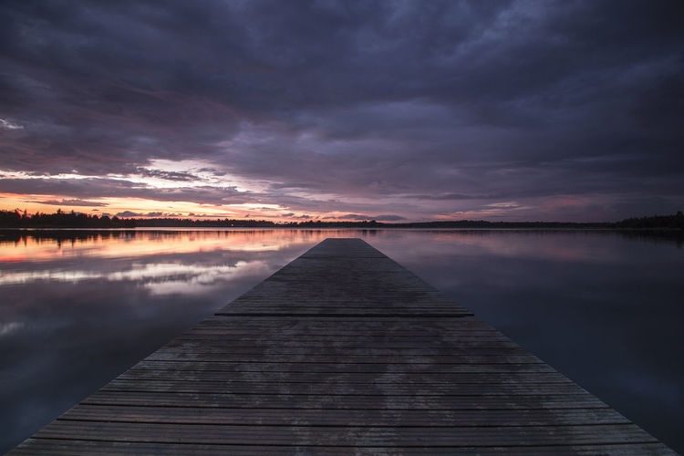 Beauty In Nature Boardwalk Calm Cloud Cloud - Sky Cloudy Diminishing Perspective Idyllic Jetty Lake Long Nature Overcast Pier Reflection Scenics Sky Sunset The Way Forward Tranquil Scene Tranquility Vanishing Point Water Weather Wood - Material