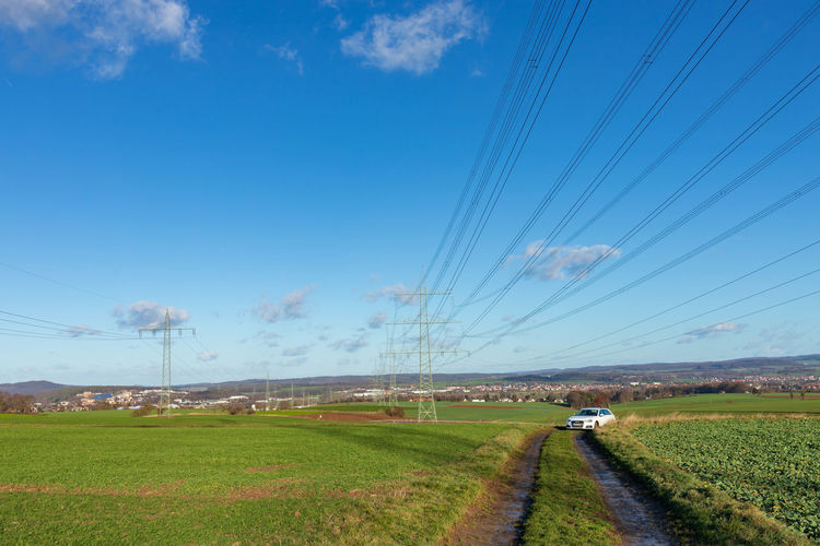 scenic view of field against sky Auto Beauty In Nature Blue Cable Cloud - Sky Day Electricity  Environment Feldweg Field Grass Januar Land Landscape Nature No People Outdoors Plant Power Line  Power Supply Scenics - Nature Sky Stromleitungen Strommast Tranquil Scene Tranquility Transportation