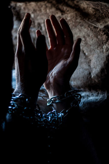 Cropped hand of person tied with chain in prison