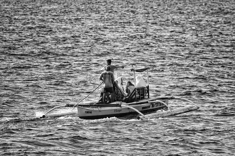 Rear view of man in fishing boat sailing in sea