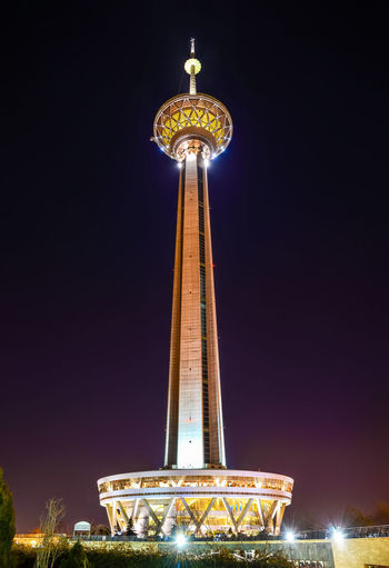 Low angle view of illuminated tower at night