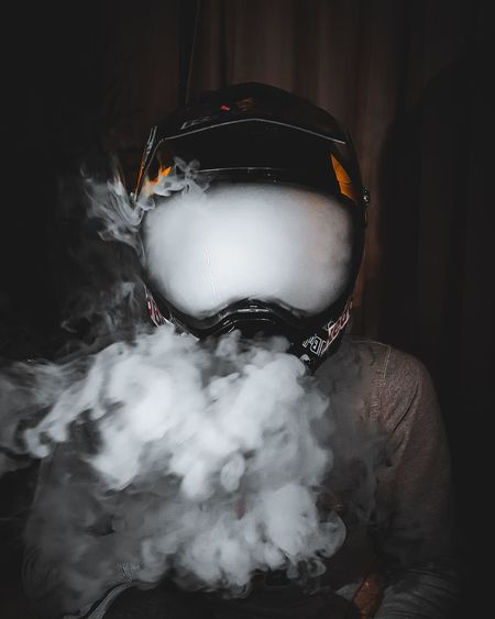 Close-up of man wearing helmet smoking against black background