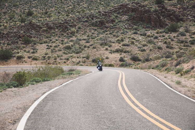 Person Riding Motorcycle On Road Against Mountains