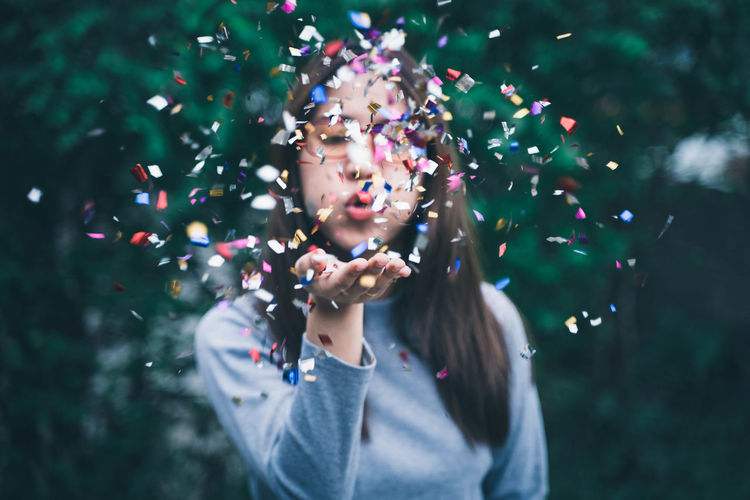 Young Woman Blowing Confetti Outdoors