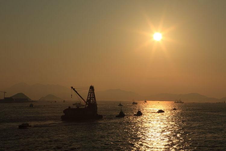 Sailboat sailing in sea at sunset