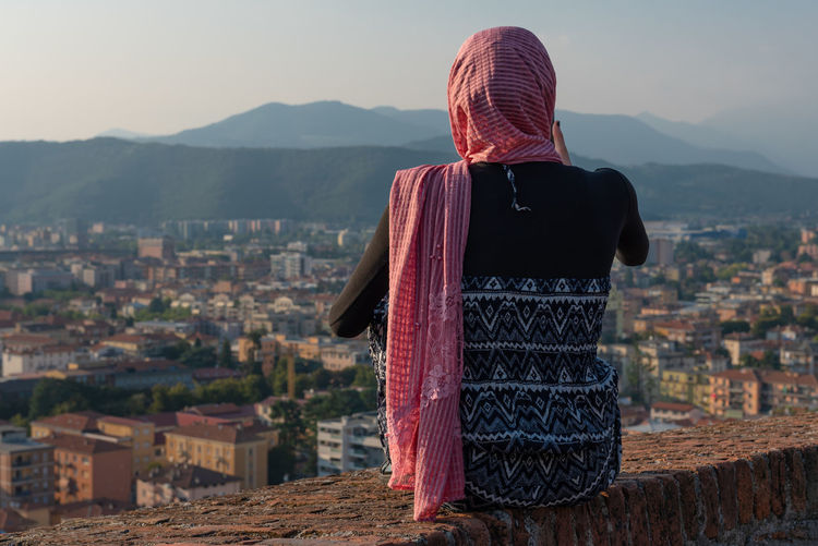 Rear view of woman looking at cityscape against sky