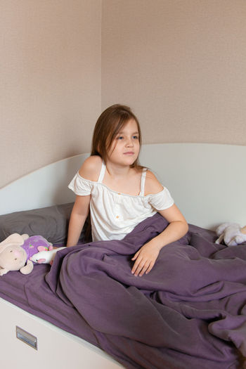 Portrait of a girl sitting on bed