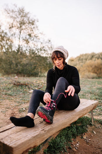 Full length of woman sitting on wood against trees