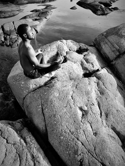 High angle view of shirtless young man mediating while sitting on rock at beach