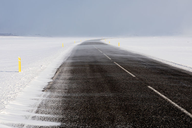 Surface level of road against sky during winter