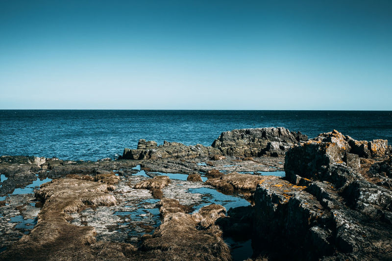 Rock formations at shore against clear blue sky