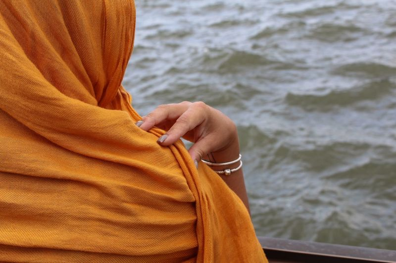 Cropped image of woman with headscarf by railing at liberty island against hudson river