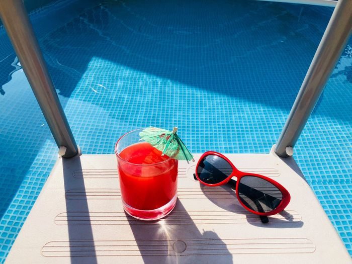 Red sunglasses and a glass of blood orange juice with a small umbrella on the stairs of a pool