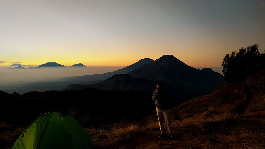 Full length of man standing on land against mountain during dawn