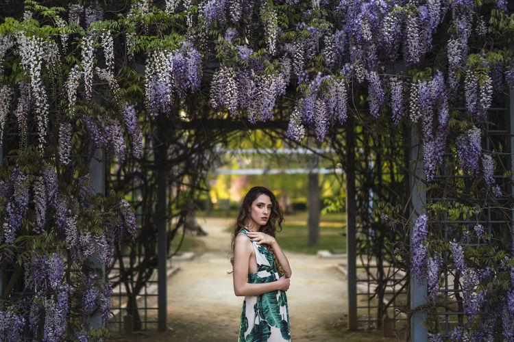 Portrait of woman standing by purple flowering plants