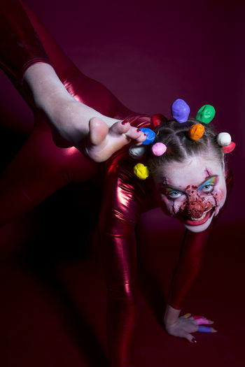 Portrait of woman with face paint wearing clown costume on colored background