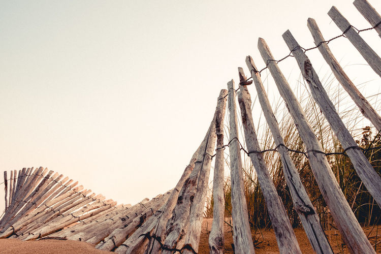 Low angle view of wooden fence at beach against clear sky