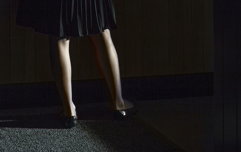 Low section of woman wearing shoes standing on carpet