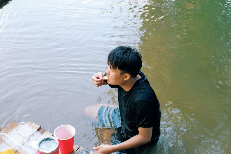 High angle view of man eating food in lake