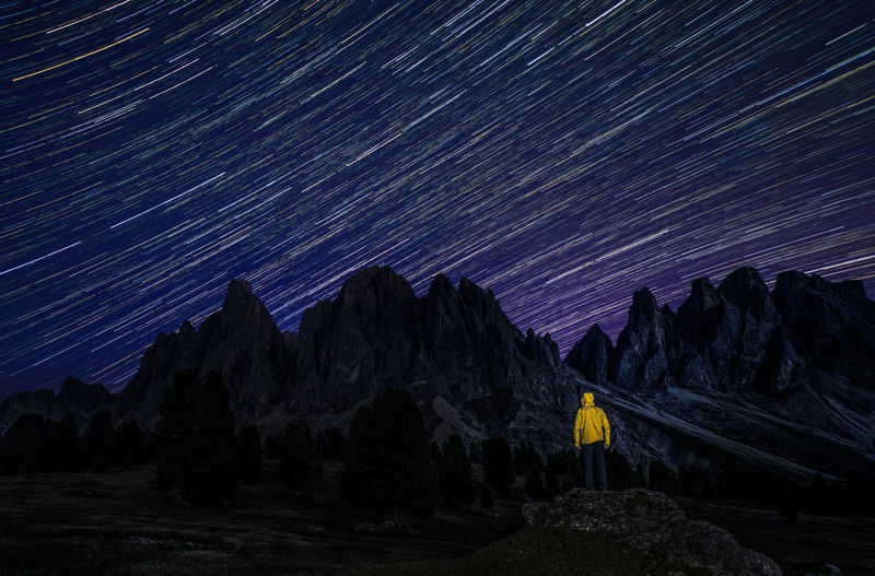 Rear view of man standing against star trail