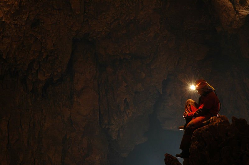 Side view of spelunker wearing illuminated headlamp in cave