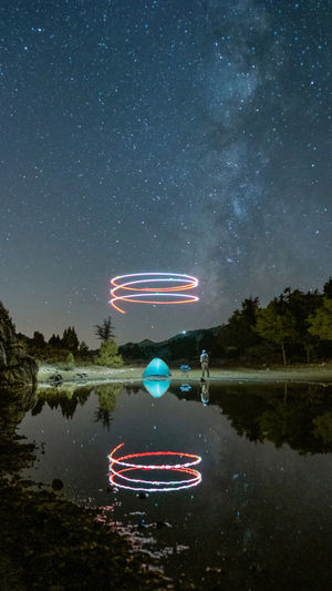 Light painting on lake against sky at night