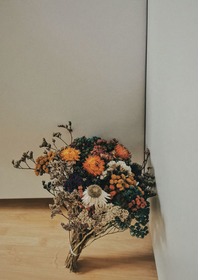 Close-up of flower vase on table against wall at home