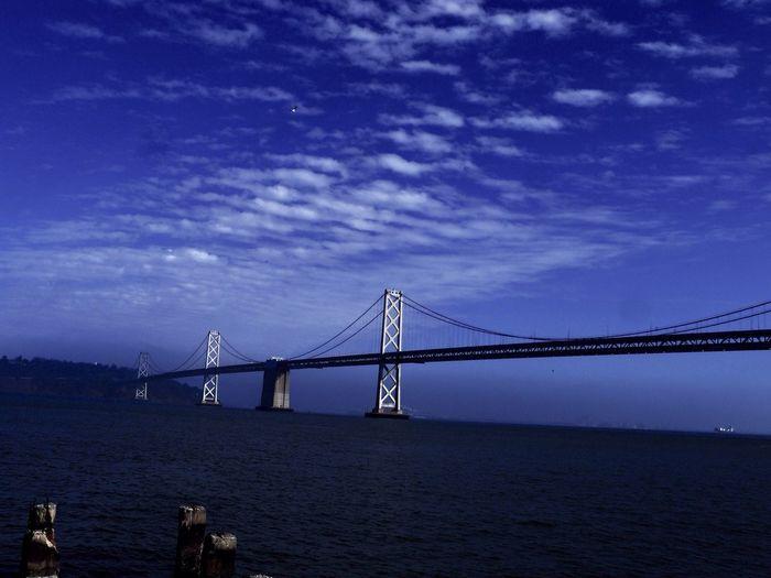 Scenic view of oakland bay bridge over sea against blue sky