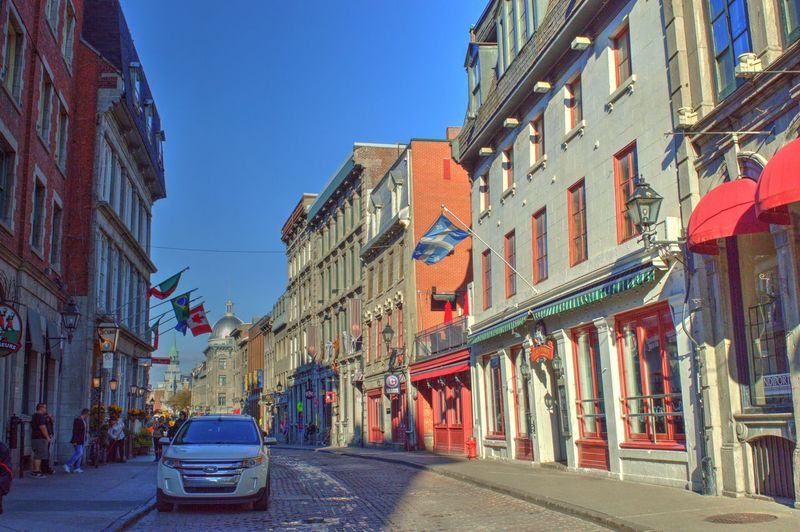 Car On City Street Amidst Buildings Against Clear Blue Sky