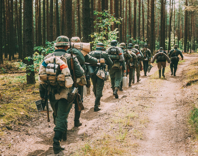 Rear view of army soldiers with equipment walking in row at forest