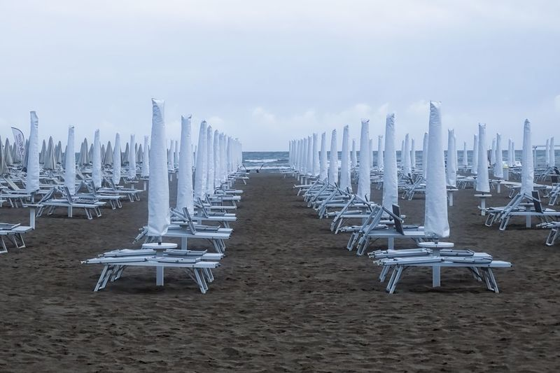 Beach umbrellas in a cloudy day Arrangement Beach Beauty In Nature Chair Day Group Of Objects Horizon Over Water In A Row Landscape Large Group Of Objects Nature No People Order Outdoors Repetition Sand Scenics Sea Sky Tranquility