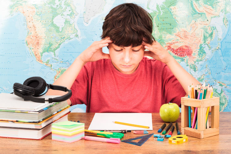 Young boy thinking about his homework Accessories Apple Books Boy Casual Clothing Child Desk Desktop Education Front View Headphones Homework Indoors  Learning Notebook Notes From The Underground One Person Person Problem School Schoolboy Solving Study Teenager Thinking