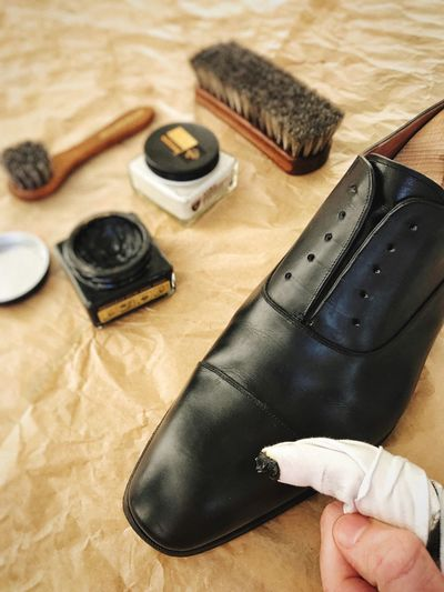 Indoors  Table Wood - Material High Angle View Workshop Shoe Human Hand Work Tool Human Body Part Shoemaker One Person Close-up Day People Leather Black Brush Cleaning Polishing Shoe Polish Shoe Shine