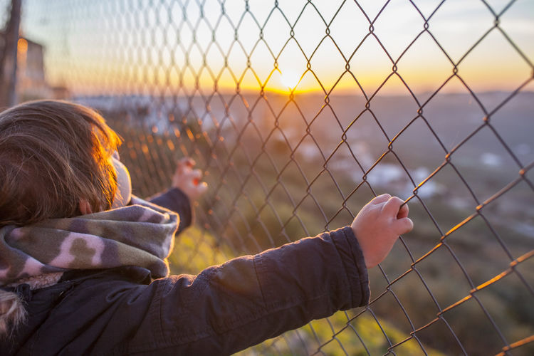 Boy standing by chainlink fence at sunset