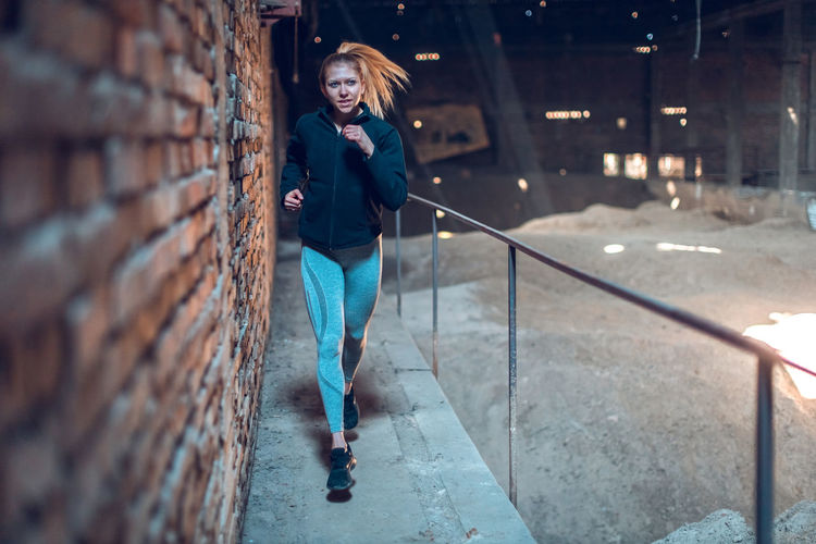 Fit young woman jogging in abandoned warehouse