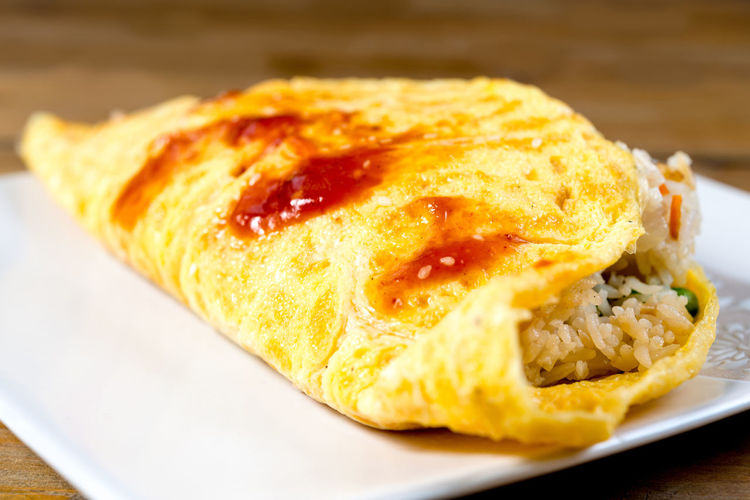 Close-up of omelet and rice wrap served in plate on table