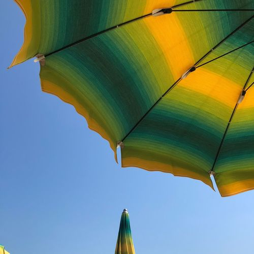 Low angle view of parasol against clear sky