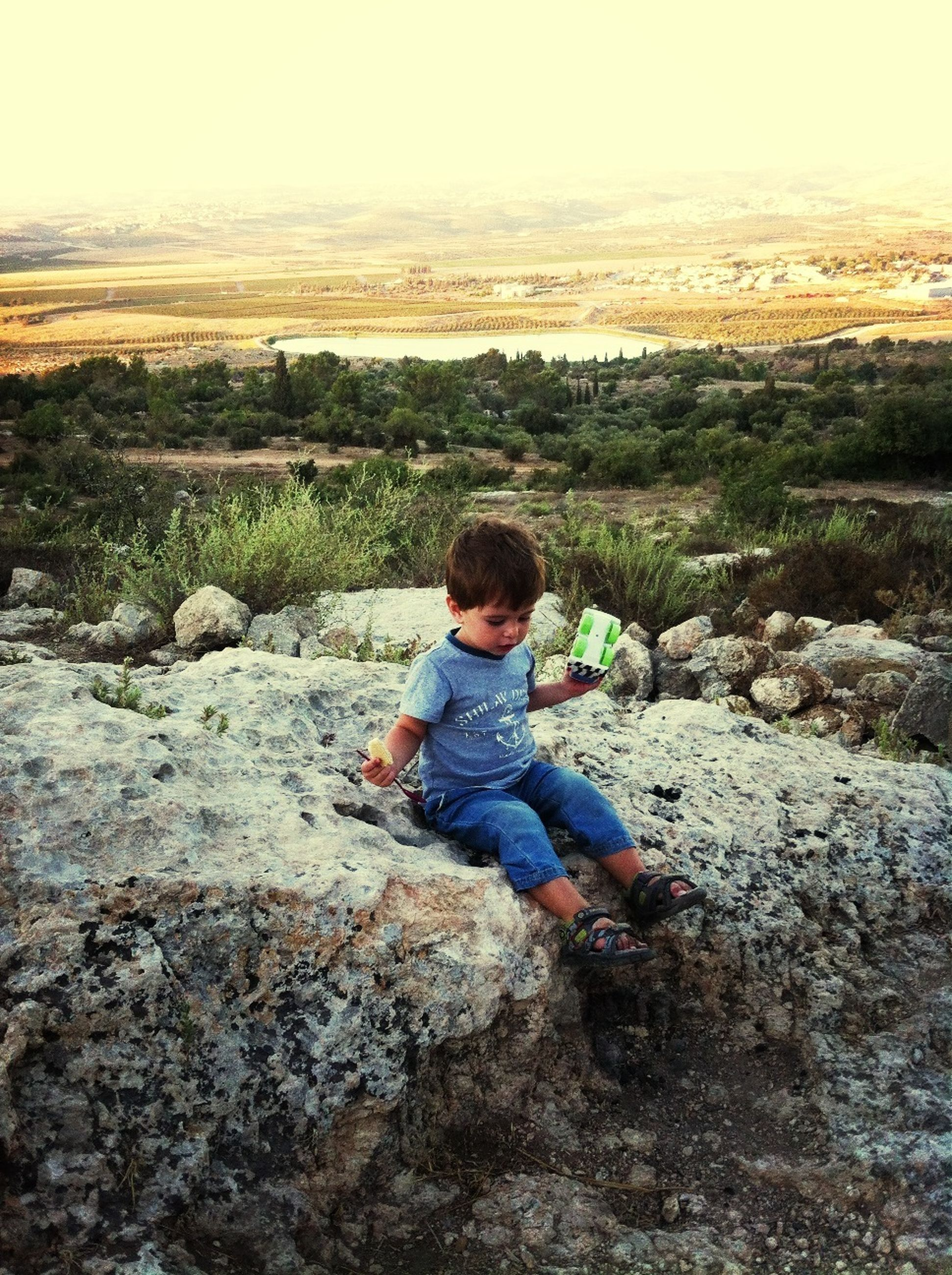 lifestyles, leisure activity, casual clothing, full length, person, childhood, elementary age, rock - object, looking at camera, boys, landscape, nature, portrait, standing, sitting, beauty in nature, sky, smiling