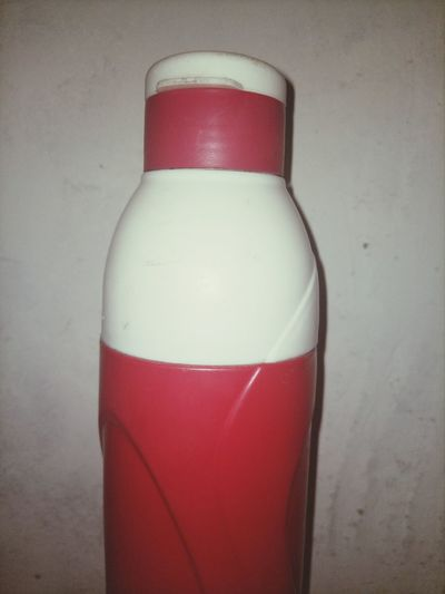Close-up of red bottle against white background