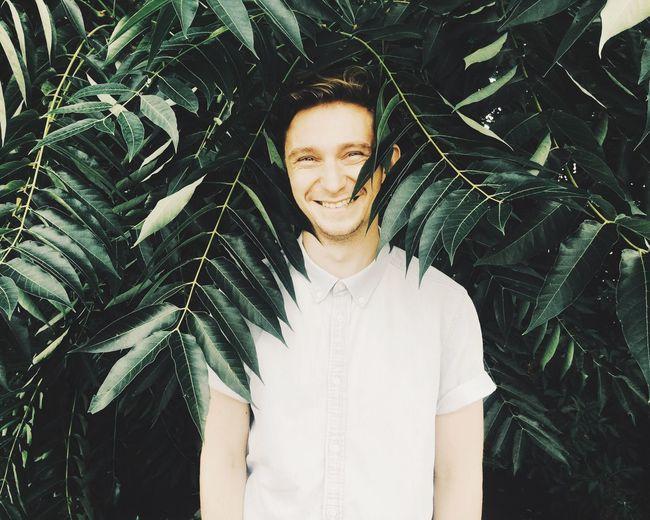 Portrait Of Smiling Man Standing Against Plants