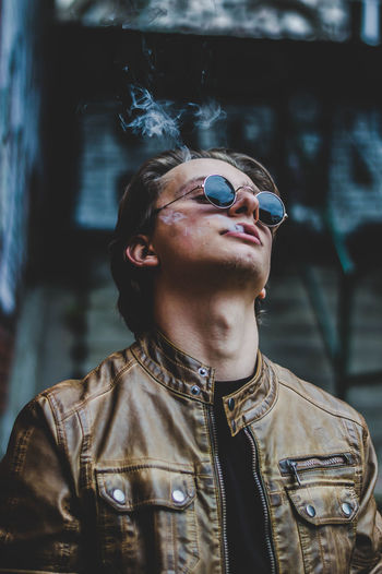 Young Man Wearing Sunglasses And Leather Jacket While Emitting Smoke From Mouth