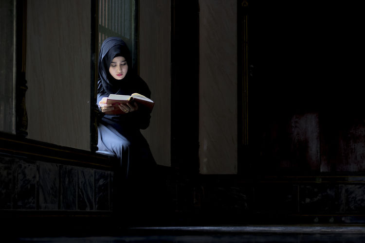 Young woman using phone while sitting on book