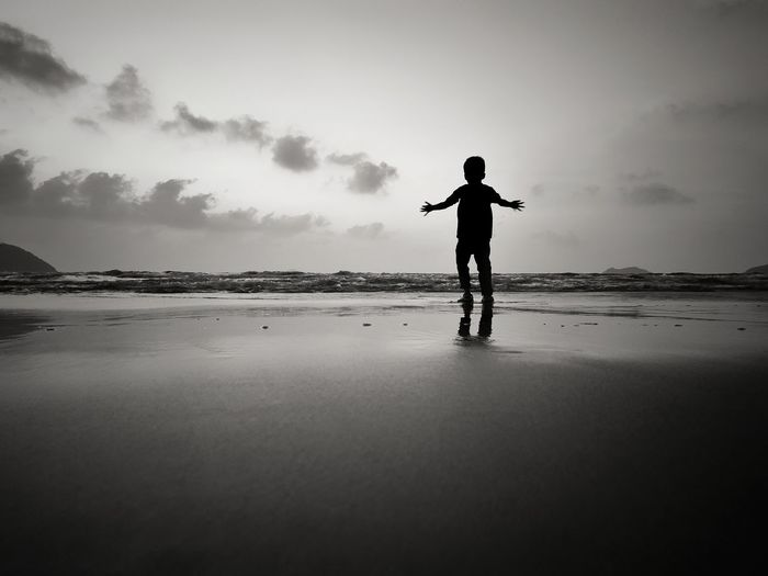 Rear view of silhouette boy standing at beach against sky