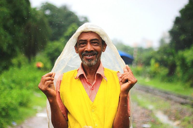 Portrait of a smiling young man in rain
