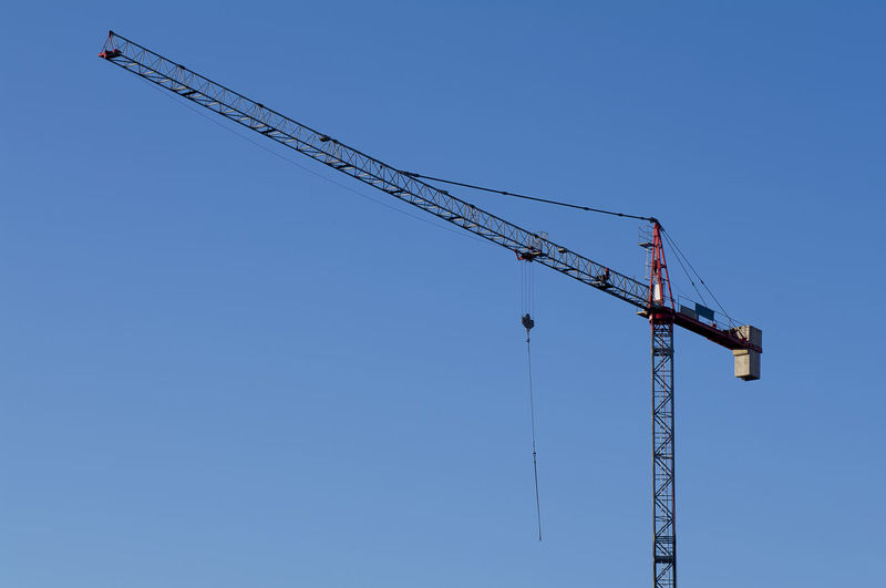 Low angle view of crane against clear blue sky