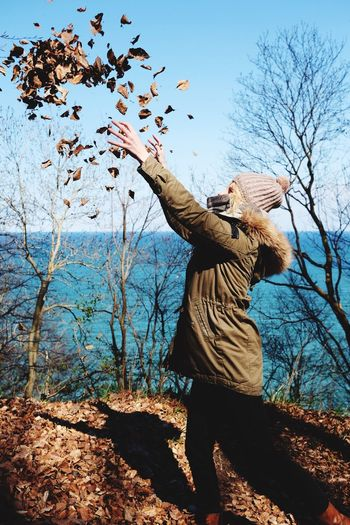 Side View Of Woman Throwing Dried Leaves On Hill By Sea Against Sky